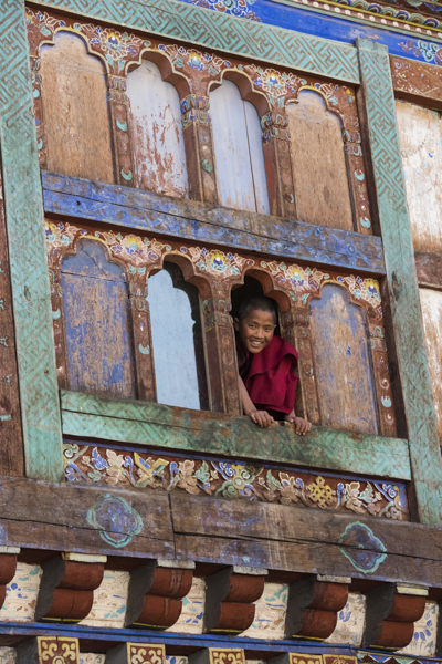 Monk poking his head out of window at Wangdicholing Palace, Bumthang, central Bhutan