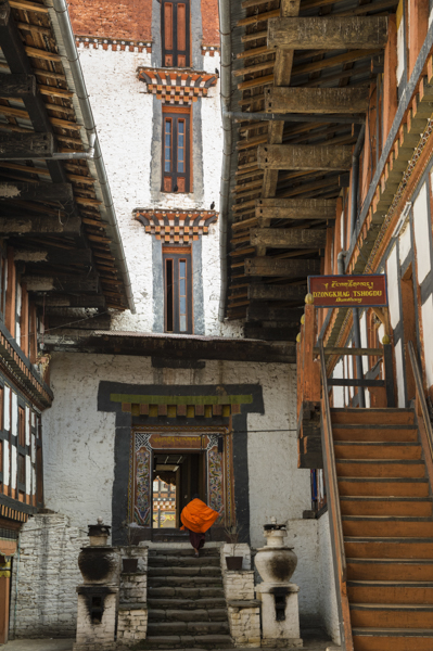 Monk running up stairs inside Jakar Dzong, Bumthang