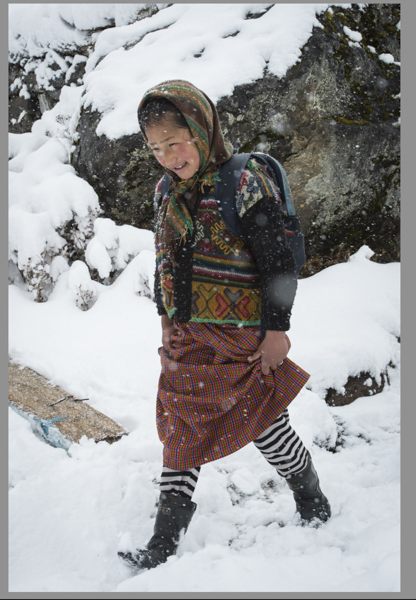 11 year old school child walking in the snow in her Kira, with leggings, a scarf, and rubber boots, and always a smile