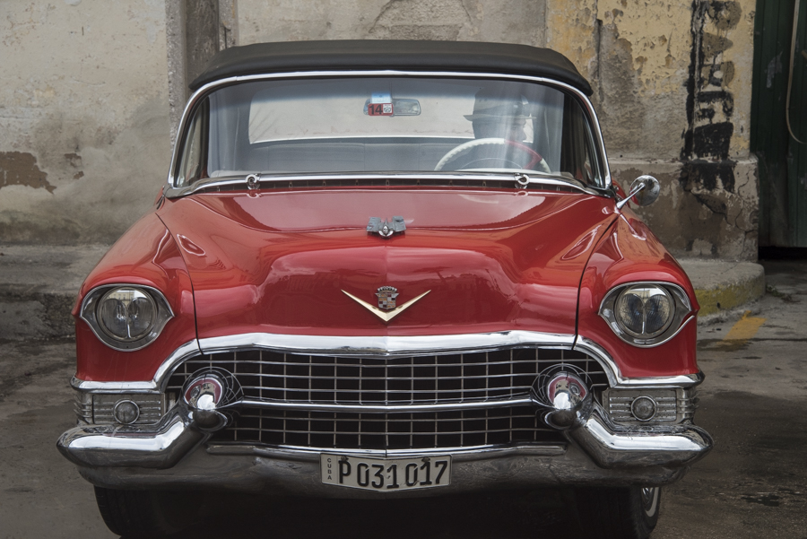 A beautifully restored red cadillac with driver wearing Cuban hat, Havana.
