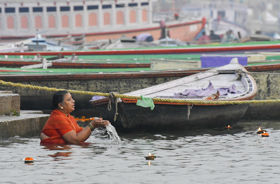 "A Hindu woman preforming a ""puja"" (ritual prayer). Hindus consider the Ganges River, the Mother Ganga as they call it,  as a goddess, and thousands of pilgrims make their offerings each dawn to the rising sun."